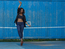 A jovem mulher na parte superior, na camisa e nos leggins nos saltos altos com composição e dança modernas do cabelo contra o azu Foto de Stock Royalty Free