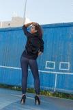 A jovem mulher na parte superior, na camisa e nos leggins nos saltos altos com composição moderna e no cabelo que levanta contra  Fotos de Stock Royalty Free