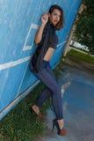 A jovem mulher na parte superior, na camisa e nos leggins nos saltos altos com composição moderna e no cabelo que levanta contra  Fotos de Stock