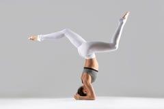 Jovem mulher na pose do headstand, fundo cinzento do estúdio Imagem de Stock