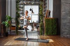 Jovem mulher na pose praticando da ioga do equilíbrio do homeware no tapete em seu quarto confortável Fotografia de Stock