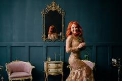 Jovem mulher na posição luxuoso do vestido no interior do vintage fotografia de stock royalty free