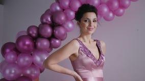 Jovem mulher na posição roxa do vestido no fundo video estoque