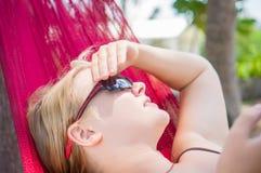 A jovem mulher na rede sob palmeiras na praia do oceano escuta MU Foto de Stock