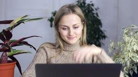 A jovem mulher na roupa da casa senta-se atrás de um portátil e mostra-se bastante os polegares acima filme
