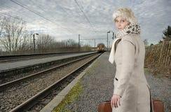 Jovem mulher na roupa do inverno que espera seu trem imagens de stock royalty free