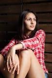 Jovem mulher na roupa do vaqueiro sobre a madeira Foto de Stock