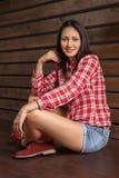 Jovem mulher na roupa do vaqueiro sobre a madeira Imagem de Stock
