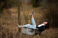 A jovem mulher na roupa está tomando um banho velho vazio no meio de uma floresta imagens de stock royalty free