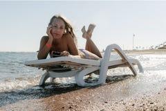 Jovem mulher na sala de estar do chaise na praia do mar A menina relaxa no bea imagem de stock