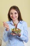Jovem mulher na sala de visitas com salada fresca fotos de stock