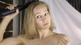 Jovem mulher na toalha que penteia seu cabelo com pente quente na frente de um espelho Termas do cuidados com a pele e os home vídeos de arquivo