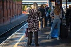 A jovem mulher nas calças de brim com cabelo louro longo está na plataforma railway que espera o trem atrasado fotografia de stock royalty free