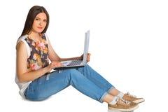 Jovem mulher nas calças de brim com o portátil que senta-se no assoalho Fotografia de Stock Royalty Free