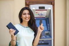 Jovem mulher nas calças de brim curtos usando uma máquina de caixa automatizado imagem de stock royalty free