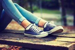 Jovem mulher nas calças de brim e nas sapatilhas azuis Fotografia de Stock Royalty Free