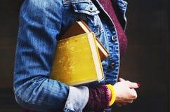 A jovem mulher nas calças de brim veste guardar livros velhos em sua mão Imagem de Stock