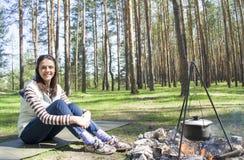 Jovem mulher nas madeiras perto do fogo com um potenciômetro foto de stock