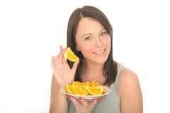 Jovem mulher natural feliz atrativa que guarda uma placa de segmentos alaranjados suculentos maduros Imagens de Stock