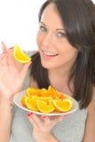 Jovem mulher natural saudável feliz atrativa que guarda uma placa de segmentos alaranjados suculentos maduros Fotos de Stock Royalty Free