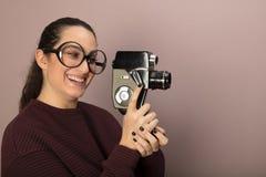 Jovem mulher Nerdy que guarda uma câmera do filme do vintage Imagens de Stock