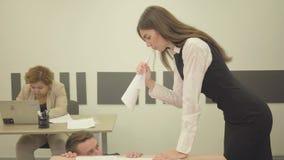A jovem mulher nervosa dobrou o papel sob a forma de um chifre e gritar no homem que se sentando sob a tabela no moderno filme