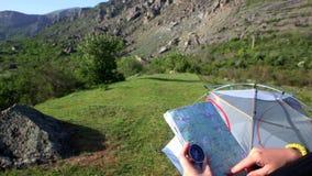 A jovem mulher no acampamento com mapa e compasso olha as montanhas e o trajeto de busca video estoque