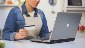 Jovem mulher no avental que introduz o número de cartão de crédito no portátil, loja do produto em linha vídeos de arquivo