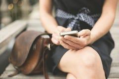 Jovem mulher no banco na cidade com telefone Fotos de Stock