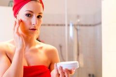 A jovem mulher no banheiro olha em um espelho Foto de Stock