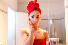 A jovem mulher no banheiro olha em um espelho Imagens de Stock Royalty Free
