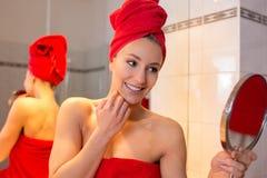 A jovem mulher no banheiro olha em um espelho Fotos de Stock