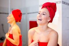 A jovem mulher no banheiro olha em um espelho Imagem de Stock Royalty Free