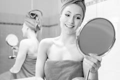 A jovem mulher no banheiro olha em um espelho Fotos de Stock Royalty Free