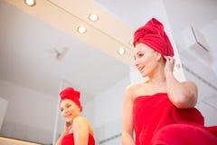 A jovem mulher no banheiro olha em um espelho Fotografia de Stock Royalty Free
