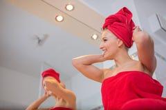 A jovem mulher no banheiro olha em um espelho Fotografia de Stock