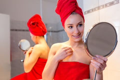 A jovem mulher no banheiro olha em um espelho Imagem de Stock