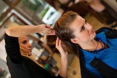 Jovem mulher no bar do cabeleireiro que tem um tratamento e um corte de cabelo Imagem de Stock Royalty Free