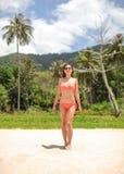 Jovem mulher no biquini e em óculos de sol vermelhos que anda na praia, selva com as palmeiras atrás dela foto de stock royalty free