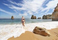 Jovem mulher no biquini na praia rochosa no por do sol, Lagos, Portugal Luz contrária Imagens de Stock Royalty Free