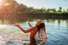 Jovem mulher no biquini que joga na água e que faz o respingo F?rias de ver?o imagem de stock royalty free