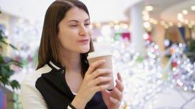 Jovem mulher no café bebendo da alameda do copo de papel marrom Decorações do White Christmas no fundo vídeos de arquivo