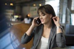 Jovem mulher no café bebendo do café e fala no telefone celular Imagens de Stock Royalty Free