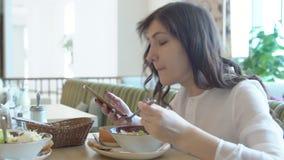 Jovem mulher no café com telefone Pausa para o almoço filme