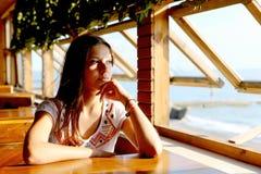 Jovem mulher no café perto do mar foto de stock royalty free
