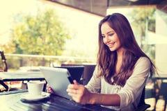 Jovem mulher no café usando a tabuleta fotos de stock royalty free