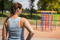 Jovem mulher no campo de jogos dos esportes no dia de verão brilhante A menina vai jogar esportes e aptidão imagem de stock
