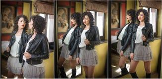 A jovem mulher no casaco de cabedal preto e o tutu curto cinzento contornam a vista em um grande espelho Levantamento encaracolad fotos de stock