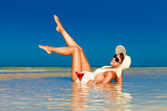 Jovem mulher no chapéu de palha que coloca na praia e no enjoyi tropicais fotografia de stock