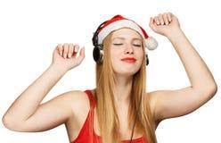 A jovem mulher no chapéu de Papai Noel e os fones de ouvido tomam o prazer de imagem de stock